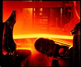 Steel strip. Strip of glowing steel being rolled in a rolling mill. Water is being sprayed onto the rollers to keep them cool. Rolling consists of tak...