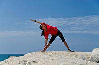 Woman in a yoga position, Trikonasana, by the sea in Kanyakumari, Tamil Nadu, India, Asia