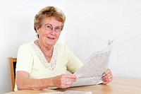 Elderly woman sitting at a table with a newspaper