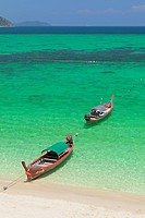 Longtail boats on sunrise beach on Ko Lipe island, part of Tarutao national marine park, Thailand