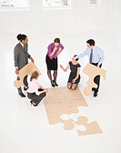 Business people doing puzzle in office