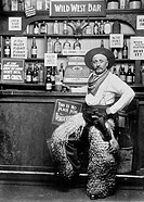 Italian American man leaning on the bar of the ´Wild West Bar´holding a jug and dressing up as a cowboy wearing weird pants´cover, a belt and guns on ...