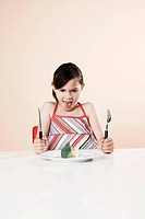 Girl holding a knife and a fork looking disgustedly at a piece of broccoli