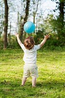 child throwing ball in midair, arms stretched out and up, from back