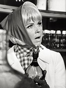 The American actress and singer Doris Day wearing a headscarfholding a bottle in her hand looking at someone with perplexity in ascene of ´Caprice´. 1...