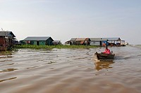 Floating villages and a man in a small wooden boat on Tonle Sap Lake, Chong Khneas, Siem Reap, Cambodia, Indochina, Southeast Asia