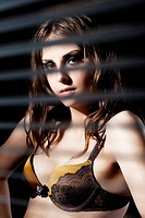 Cute woman in bra hide behind venetian blind