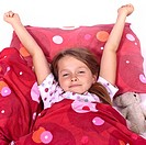 an eight_year_old girl in bed with blanket and pillows and stuffed animals