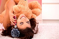 Attractive girl laying on floor at home, hugging huge teddy bear, chatting on mobile.