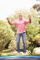 Senior Man Jumping On Trampoline In Garden
