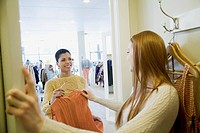 Pretty, young woman trying on clothes.