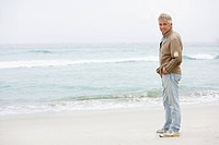 Senior Man On Holiday Standing On Winter Beach