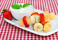 Healthy fresh fruit on kabobs with a side yogurt dip.