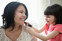 Young daughter braiding mom's hair