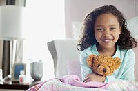 Young girl in bed with teddy bear.