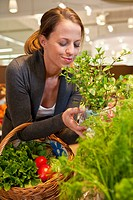 Woman smelling fresh herbs in supermarket