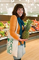 Young smiling woman holding pineapple in supermarket