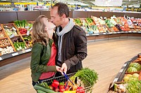 Couple kissing at shopping in supermarket