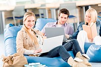 Group of young high_school students relaxing with laptop and book