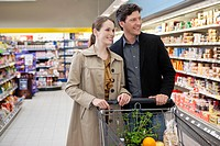Smiling couple doing shopping in supermarket