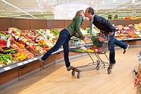 Couple kissing in supermarket