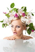 young sexy beautiful woman with naked shoulder and wearing a big crown of flower and leaves as spring queen. She is behind the table, her face is turn...