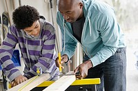 Father teaching son how to use tools.