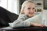 Portrait of cute young blond girl on couch