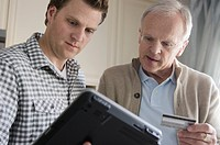 Son helping senior father with internet transaction.