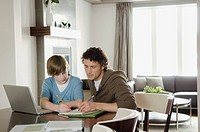 Dad helping son with homework.