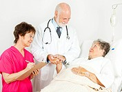 Doctor and nurse treating senior woman in the hospital.