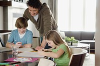 Dad helping kids with homework.