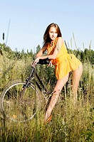 Young beautiful woman with bike on the meadow