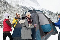 Young adults setting up tent in winter