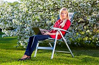 outdoor portrait of beautiful blonde girl sitting in folding chair on green grass near bloomin apple tree with laptop