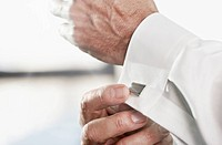 Close up of businessman's hands attaching cuff link (thumbnail)