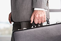 Close up of businessman's hand carrying briefcase (thumbnail)