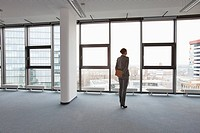 Businesswoman standing in empty office (thumbnail)