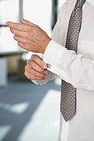 Business man doing up his cuffs (thumbnail)