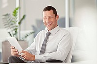 Portrait of smiling businessman holding digital tablet