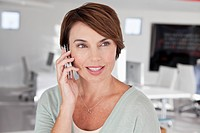 Smiling businesswoman talking via cell phone (thumbnail)