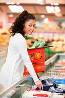 Young smiling woman buying frozen food in grocery store