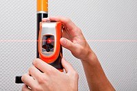 Man hands measuring with laser level gage