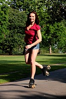 Fun leisure activity for fit beautiful young athletic woman roller skating through the park in summer sunshine. She is wearing a red top and denim cut...