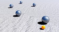 Five metallic petanque balls and the small yellow jack on the ground by day light