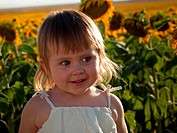 Little girl playing in sunflower field.