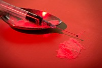 Narcotic disposable syringe and spoon on red background