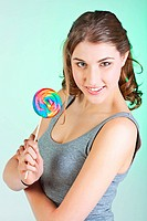 Portrait of smiling teenager girl holding colorful lollipop