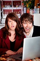 Angry woman shocked with spouse over something on a laptop