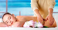 Young woman relaxing in spa salon and getting massage of body _ nature background